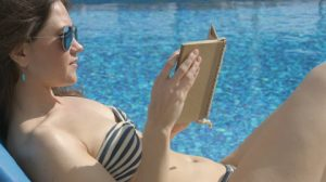 baca buku disekitar kolam renang